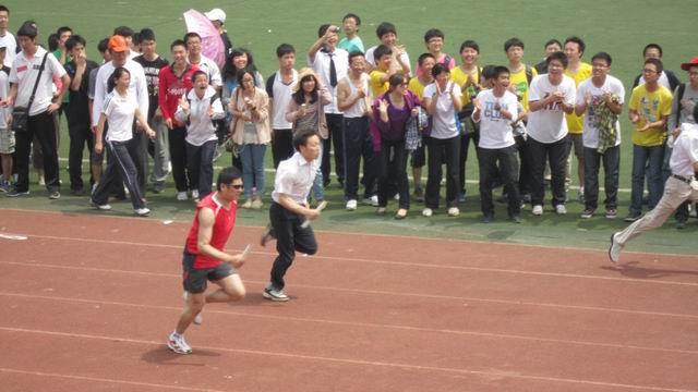 本次运动会的最后一个项目是教师20*60迎面接力比赛。今天上午11点,老师们身着运动服,整齐地排列在运动场跑道的正中心。高一三部的20位参赛老师在甘祥生主任、鲁志祥副主任的指导下排好接力顺序,活动筋骨,跃跃欲试。这里面有男子100米冠军的获得者黄发享老师、女子100米第二名和第三名的获得者熊效华老师、聂姣平老师,还有老当益壮的冯辉老师、黎昌林老师。